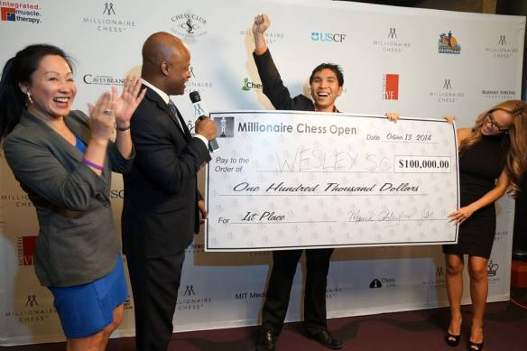 Wesley So exults after receiving a replica of the $100,000 first prize from Millionaire chess organizer Maurice Ashley at Planet Hollywood Resort & Casino PHOTO BY PAUL TRUONG.